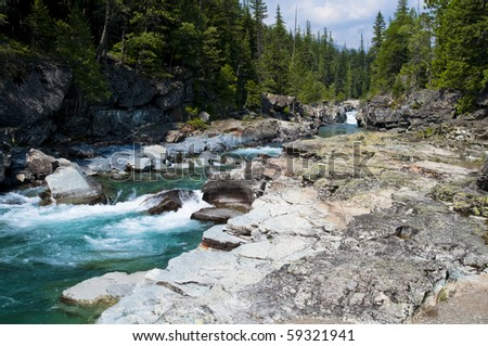 Turquoise river flowing towards Lake McDonald at Glacier National Park - stock photo