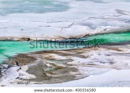 Turquoise snowmelt water begins to break apart the thick ice that covered the glacial Delta River in the Alaska Range all winter - stock photo