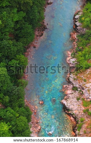 Turquoise stream of water flowing at the bottom of a canyon - stock photo