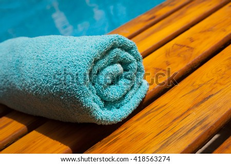 turquoise towel on a lounger by the blue pool - stock photo