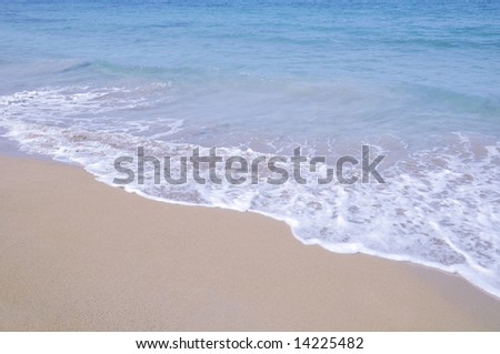 Turquoise tropical waters washing on a pristine sand beach