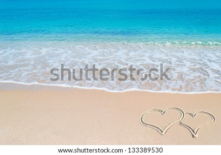 turquoise water and golden sand in Sardinia with two hearts drawn in the sand