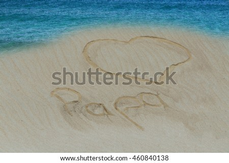 Turquoise water and golden sand with a subscribed in the sand heart and the word Dad in German.