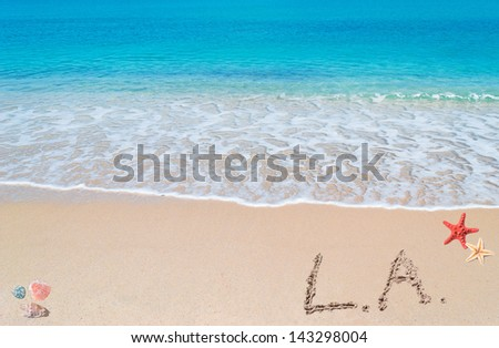 """turquoise water and golden sand with shells and sea stars and """"l.a."""" written on it - stock photo"""