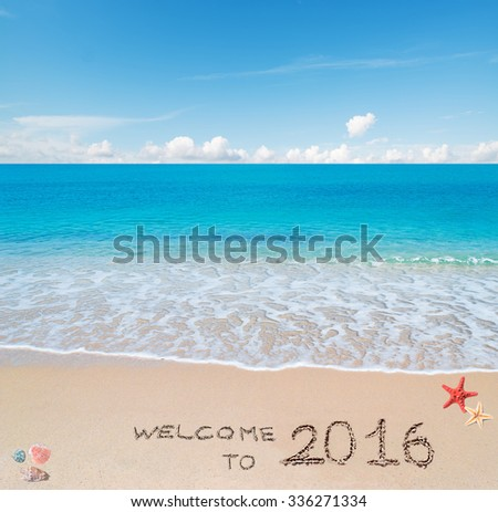 """turquoise water and golden sand with shells and sea stars with """"welcome to 2016"""" written on it - stock photo"""