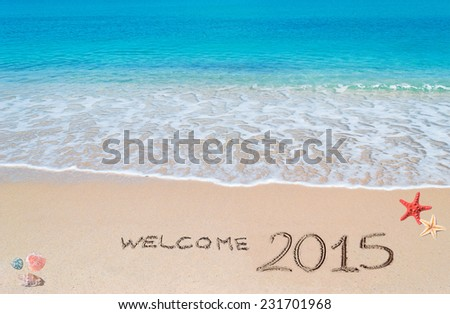 """turquoise water and golden sand with shells and sea stars with """"welcome 2015"""" written on it - stock photo"""