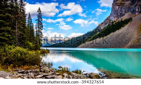 Turquoise water of Lake Louise in Banf National Park in the Canadian Rocky Mountains under a beautiful blue sky with a few clouds - stock photo