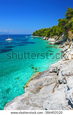 Turquoise waters with cliffs and anchoring sailboats in the neighborhood of Kastani beach (another filming location of Mamma Mia! musical), Skopelos island, Greece  - stock photo