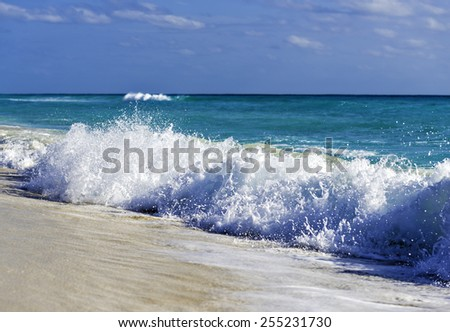 Turquoise waves crashing on white sand beach - stock photo