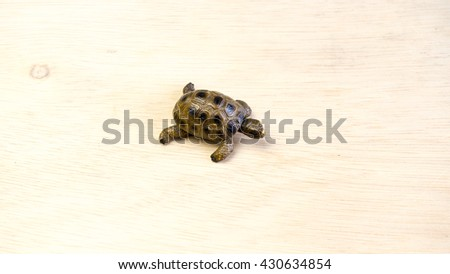 Turtle or tortoise miniature on empty wooden surface. Concept of endangered species. Slightly de-focused and close-up shot. Copy space. - stock photo