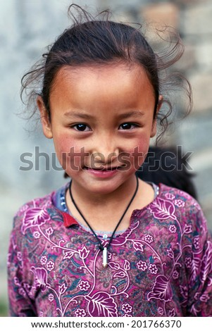 TURTUK, INDIA - JUNE 13: Balti shoolgirl Aminar, 8, poses for a photo during Turtuk festival on June 13, 2012 in Turtuk Village, Ladakh, India. Turtuk village opened to foreign tourists in 2010. - stock photo