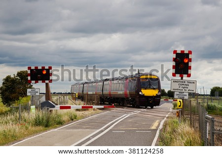 TURVES, UK - JULY 8: A Cross Country operated class170 diesel commuter service crosses an automatically operated level crossing on July 8, 2015 in Turves. Cross Country operate 29 class 170 Turbostars