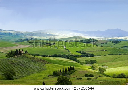 Tuscan plain before the rain. Rural house on the hill among vineyards - stock photo