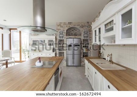 Tuscany - countertop, commode and refrigerator in kitchen - stock photo