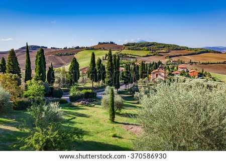 Tuscany countryside landscape with cypress trees, farms and green fields, Italy. View from Monticchiello - stock photo