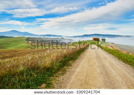 TUSCANY, ITALY - OCTOBER 17, 2016: Scenic landscape with beautiful fields, meadows and hills with morning fogs, Italy