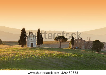 Tuscany landscape at sunrise with a little chapel of Madonna di Vitaleta, San Quirico d'Orcia, Italy - stock photo