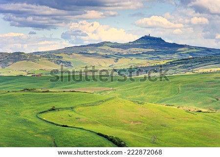 Tuscany, Radicofani village on hilltop, farmland and green fields. Val d Orcia, Italy, Europe. - stock photo