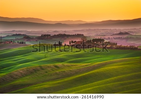 Tuscany, rolling hills on sunset. Crete Senesi rural landscape and sunlight. Green fields, a farm with trees. Siena, Italy - stock photo