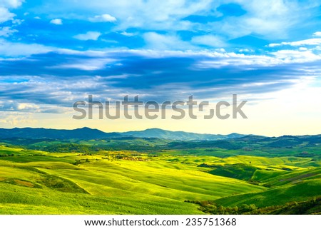 Tuscany, rural sunset landscape. Countryside farm, cypresses trees, green field, sun light and cloud. Volterra, Italy, Europe.