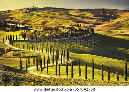 Tuscany, rural sunset landscape. Countryside farm, cypresses trees, green field, sun light and cloud. Italy, Europe. - stock photo