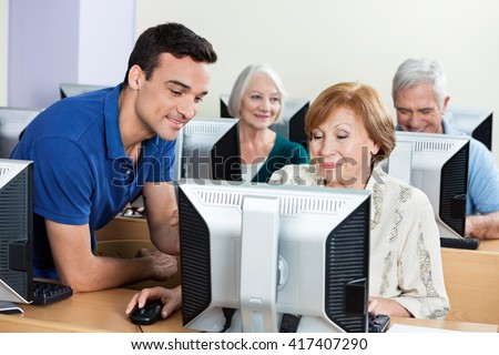 Tutor Assisting Senior Woman During Computer Class