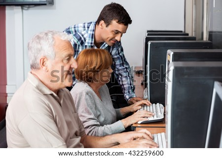 Tutor Assisting Senior Woman In Using Computer - stock photo