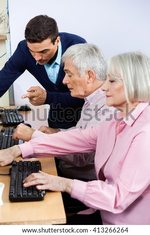 Tutor Explaining Senior Students Using Computers In Classroom - stock photo