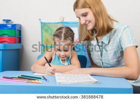 Tutor sees that the child turns out to write letters of the alphabet - stock photo