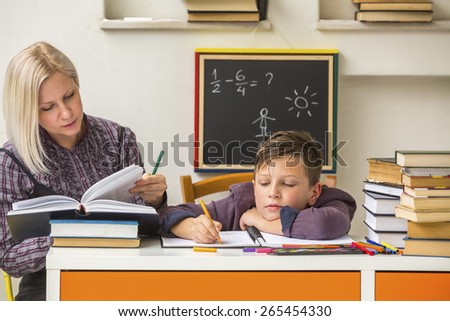 Tutor teaches a school Boy with his studies. - stock photo