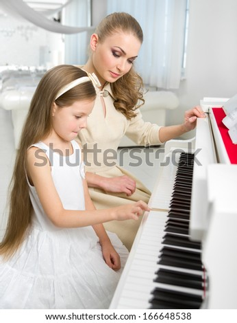 Tutor teaches little girl to play piano. Concept of music study and creative hobby - stock photo