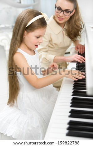 Tutor teaches little girl to play piano. Concept of music study and enjoyment - stock photo