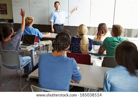 Tutor With High School Students In Class Using Laptops - stock photo