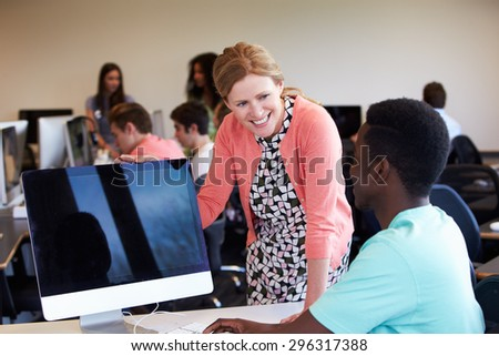 Tutor With Male College Student In Computer Class - stock photo