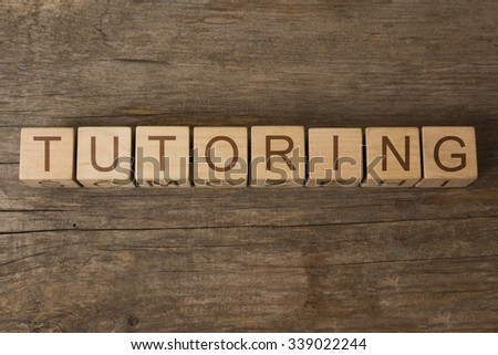 TUTORING text on a wooden background - stock photo
