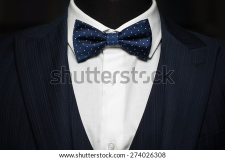 Tuxedo and bow tie on the unrecognizable person - stock photo