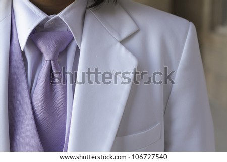 Tuxedo / Standing groom in a white  tuxedo. Image was taking during a wedding.