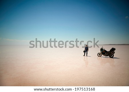 TUZ GOLU, TURKEY - AUGUST 25: Man with his bike at salt lake(Tuz Golu) on august 25, 2013, Turkey. - stock photo