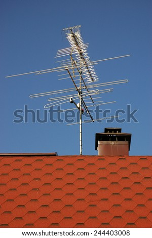 TV antenna on roof-top of a house against bright blue sky background - stock photo