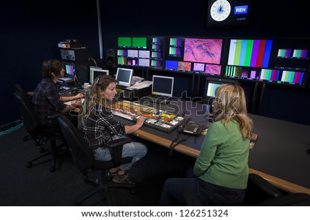 TV Director talking to her Vision Mixer in a Television Gallery. - stock photo