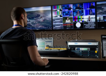 TV engineer at editor in studio. TV editor working with vision mixer in a television broadcast gallery.Man sat at a vision mixing panel in a television studio gallery - stock photo