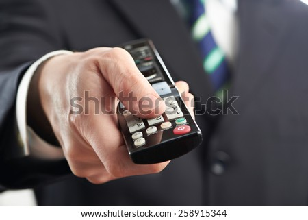 TV remote control in hand of businessman isolated on white - stock photo