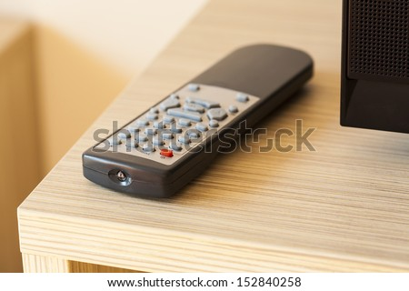 TV remote control lying on the counter, visible part of the TV. - stock photo