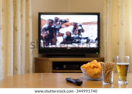 TV, television watching (american troops, war movie) with snacks lying on the table - stock photo - stock photo