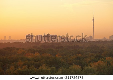 TV tower and urban houses in warm summer orange sunrise in early morning, Moscow - stock photo