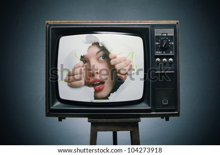 TV with a picture of a girl, his eyes through the hole.
