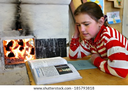 Tver, Russia - May 2, 2006: Russian schoolgirl, Schegoleva Tanya, 11 years old,  reads textbook sitting beside an open fire wood stove. - stock photo