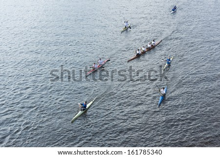 TVER, RUSSIA - OCT 11: Rowers accompanying the Olympic torch during the two phases of the relay passing on the water on October 11, 2013