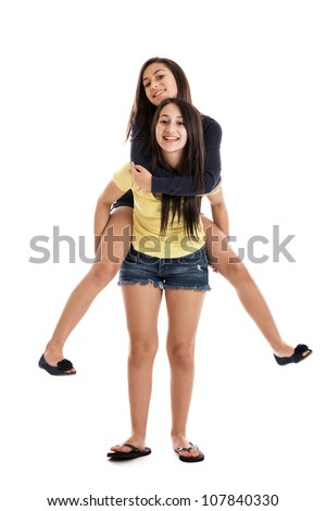 Tween and teen sisters on piggyback ride isolated on white background - stock photo