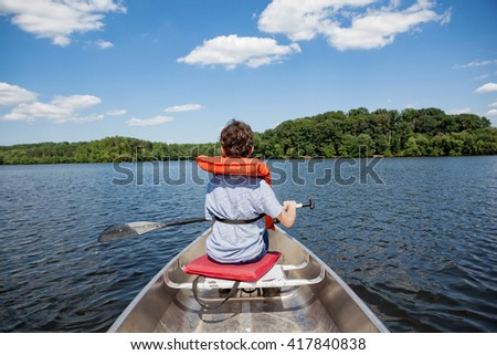 Tween boy rowing in a boat with oar on a lake in summertime